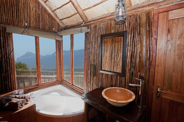 tree house bathroom with tub sink toilet and outside shower