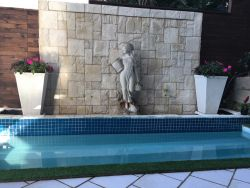 Swimming pool and water feature wall during the day
