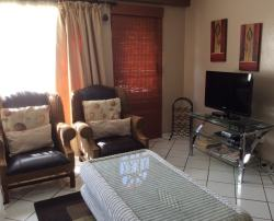 Lounge area has a 3 seater couch and 2 single chairs. There is a 32cm flat screen TV with full DSTV and DVD player.