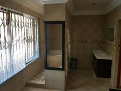 Large bathroom en-suite with corner bath and shower