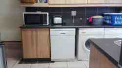 Scullery with dishwasher, washing machine, tumble dryer, iron and ironing board