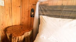 We pay close attention to the details in the Cabin. The bedside tables are hand made from invasive wood on the property. The lanterns are also hand made and dimmable, for a more relaxing and pleasant sleeping experience.