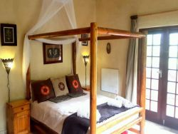 The Cozy Corner's four poster double bed stepping out onto an adjoined patio.