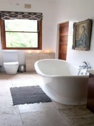 The Artisitc Cove's en-suite bathroom with bath, shower, toilet and basin.