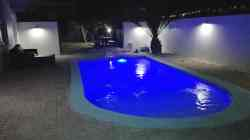 Swimming Pool at night with garden and braai area beyond