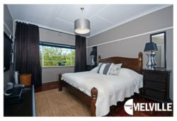 Double bedroom with LCD satellite-enabled television - at 25 8th Avenue, Melville, Johannesburg