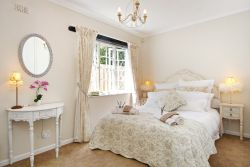 French room with Queen extra length bed. This elegant bedroom leads onto the family bathroom