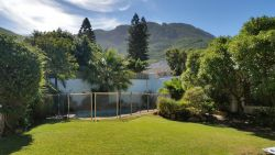 Spacious fully enclosed garden with a safety fence for toddlers around the pool and beautiful mountain views