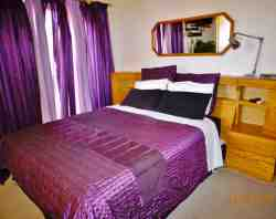 Main en-suite bedroom with private balcony, flat screen TV, dressing table & room