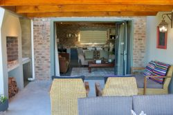 Covered stoep with braai leading into open-plan kitchen/lounge through stacking doors