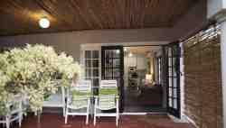 Covered verandah with large doors that opn up across the width of the lounge