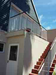 Frontal view, one flight of stairs up, parking in front of stairs). Owner's garage underneath.