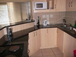 Kitchen equipped with stove, microwave, kettle & toaster and fridge