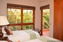 Second bedroom en-suite upstairs with private balcony and indigenous bush views