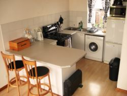 Fully equipped open plan kitchen with stove & oven, frontloader ashing machine, microwave, and fridge freezer.