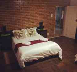 Room 1 - Self-catering Unit. This room has 2 single beds and a Queen bed. It has a separate kitchen and a full bathroom.