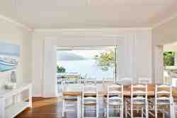 The dining table, adjoining the open-plan kitchen, leads to the covered balcony