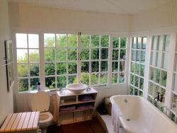 The en-suite Guest Bathroom has a bath and a shower with windows on two sides that look onto the garden