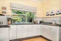 Separate kitchen with microwave, two plate stove, fridge and freezer, sink, kettle, crockery and cutlery.