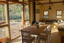 Red Rock Cottage - The dining and living room with large glass patio doors opening onto a shaded patio and braai area