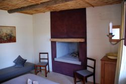 Red Rock Cottage - the Fireplace and bench which can sleep a child in the first bedroom