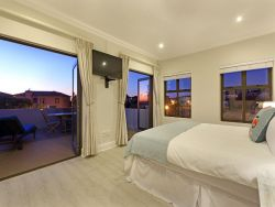 Master bedroom, king size bed, extra length, TV with DSTV, balcony with sun lounger and table, En-suite bathroom