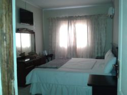 Spacious furnished room with Air conditioner, DSTV, internet Access (Wi-Fi) and tea/coffee table. Room comes with a King bed.