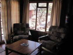 Self Catering chalet with open plan lounge/kitchenette leading  onto veranda and braai