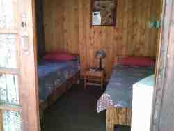 Rustic Wooden Cabin for 2 guests with shared ablutions. Offers a fridge, braai and coffee