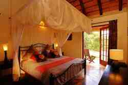 Bedroom 1 All bedrooms have airco, ceiling fans and en-suite bathrooms. There are mosquito nets. All bedrooms have doors to the wraparound terrace. This room has view over the private waterhole and the garden.