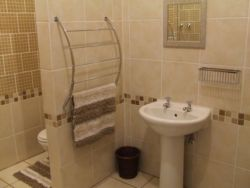 The bathroom consists of a large shower, a toilet, washbasin and comfortable dressing table.
