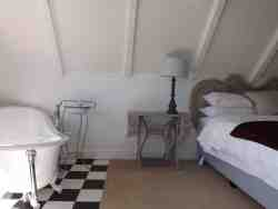 loft room with kingsize bed open plan bathroom with slipper bath with stunning view of mountains