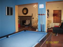 Pool table area with dart board leads out into pool area.