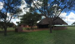 Thatched roof entertainment area next to the swimming pool, overlooking a waterhole.